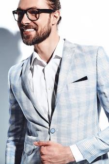 Portrait de beau mode élégant hipster homme d'affaires modèle habillé en élégant costume bleu clair dans des verres sur blanc.