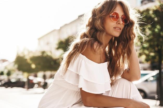 Portrait de beau modèle adolescent blond mignon sans maquillage en été hipster robe blanche vêtements assis sur le fond de la rue