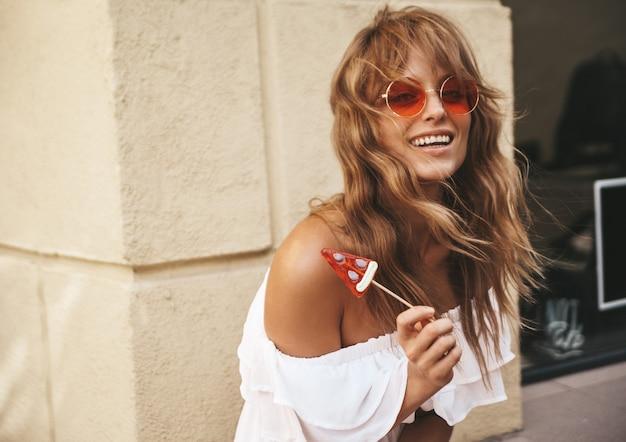 Portrait de beau modèle adolescent blond mignon sans maquillage en été hipster robe blanche vêtements avec des bonbons pastèque posant près du mur jaune