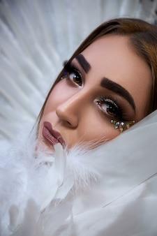 Portrait d'un beau modèle aux ailes blanches. le fond est noir