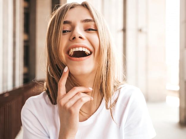 Portrait de beau modèle blond souriant vêtu de vêtements d'été hipster.