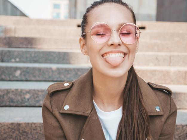 Portrait de beau modèle brune souriante vêtue de vêtements de veste d'été hipster montrant sa langue