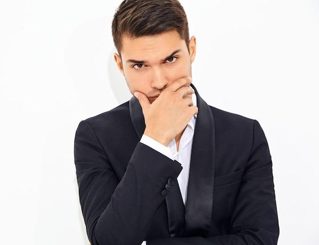 Portrait de beau modèle élégant homme d'affaires de mode vêtu d'un élégant costume classique noir. toucher son menton