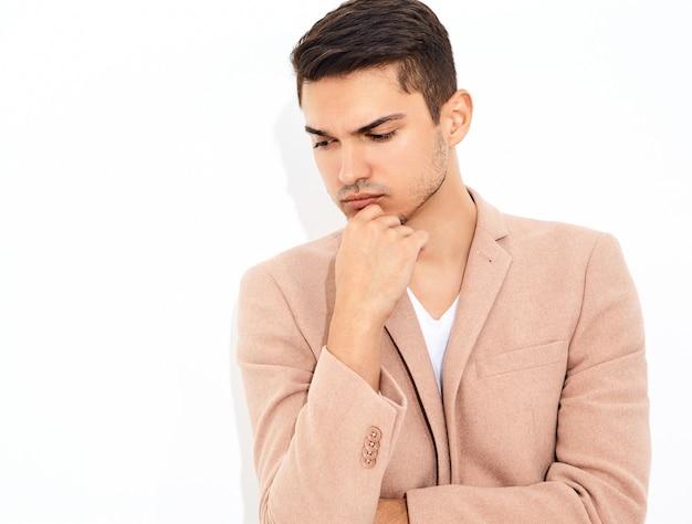 Portrait de beau modèle élégant homme d'affaires de mode vêtu d'un élégant costume rose clair posant. métrosexuel