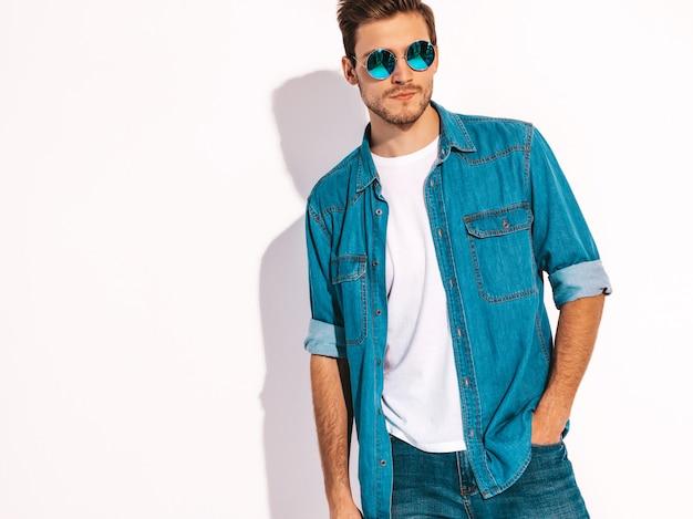 Portrait de beau modèle élégant jeune homme souriant portant des vêtements jeans et des lunettes de soleil. homme de mode