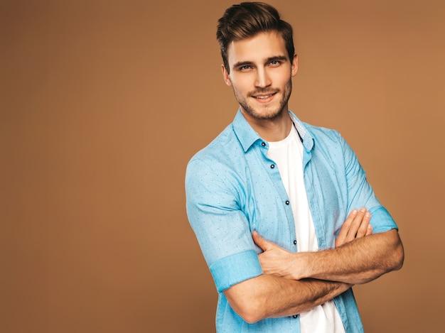 Portrait de beau modèle élégant jeune homme souriant vêtu de vêtements de chemise bleue. homme de mode posant. les bras croisés