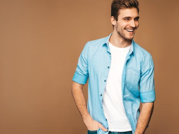 Portrait de beau modèle élégant jeune homme souriant vêtu de vêtements de chemise bleue. homme de mode posant