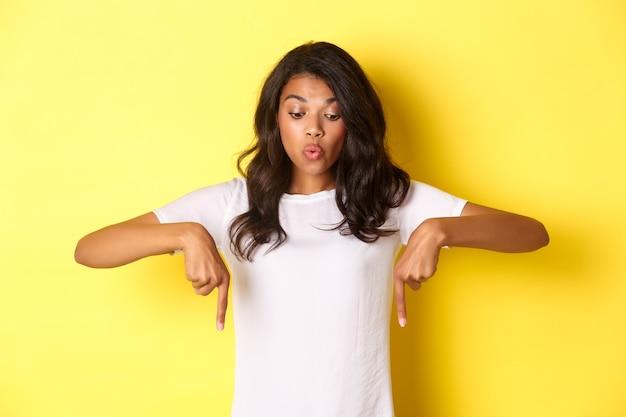 Portrait de beau modèle féminin afro-américain amusé en t-shirt blanc disant wow