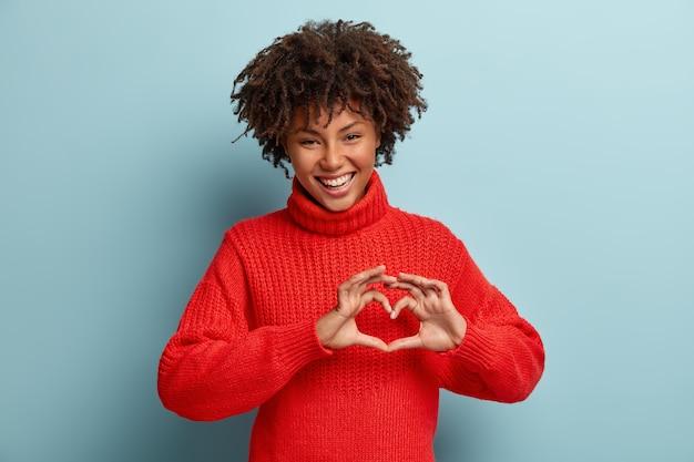 Portrait de beau modèle féminin fait un geste de coeur, dit être ma saint-valentin, démontre le signe de l'amour