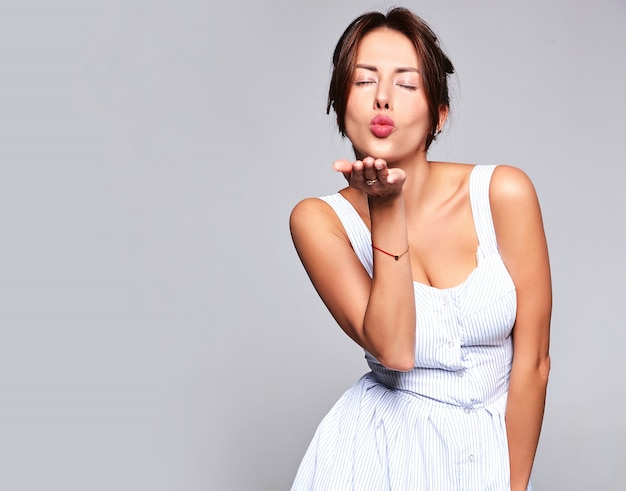 Portrait beau modèle femme brune mignonne en robe d'été décontractée sans maquillage isolé sur gris. donner un baiser