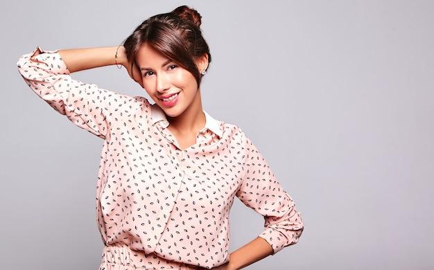 Portrait de beau modèle de femme brune mignonne souriante dans des vêtements d'été décontractés sans maquillage isolé sur mur gris