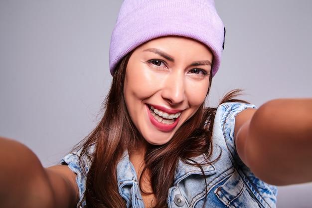 Portrait de beau modèle de femme brune mignonne souriante dans des vêtements de jeans d'été décontractés sans maquillage en bonnet violet faisant photo selfie sur téléphone isolé sur gris