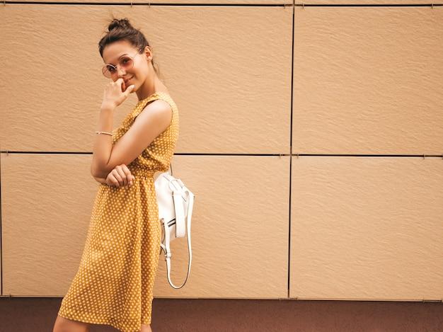 Portrait de beau modèle hipster souriant vêtu d'une robe d'été jaune. fille branchée posant dans la rue. femme drôle et positive s'amuser