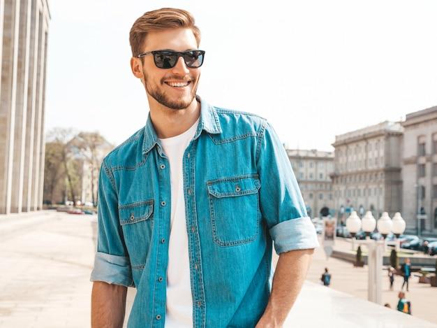 Portrait de beau modèle d'homme d'affaires lumbersexual hipster élégant souriant. homme vêtu de vêtements veste jeans.