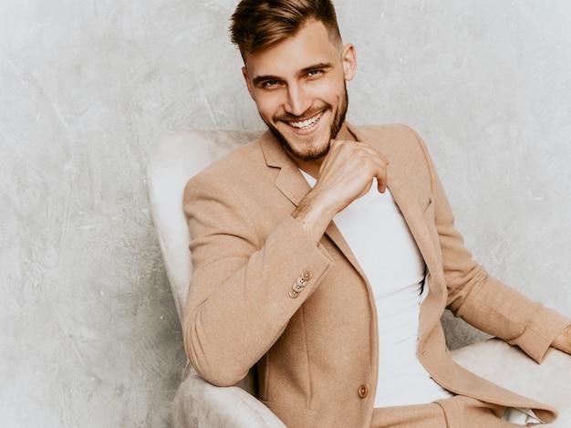 Portrait de beau modèle d'homme d'affaires souriant hipster portant un costume beige décontracté. assis sur une chaise à l'intérieur