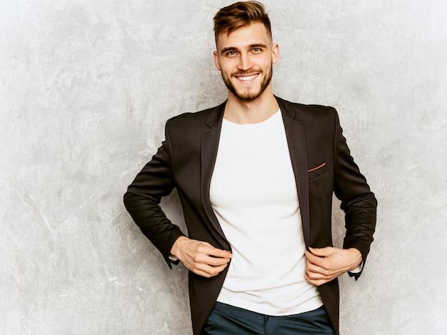 Portrait de beau modèle d'homme d'affaires souriant hipster portant un costume noir décontracté.
