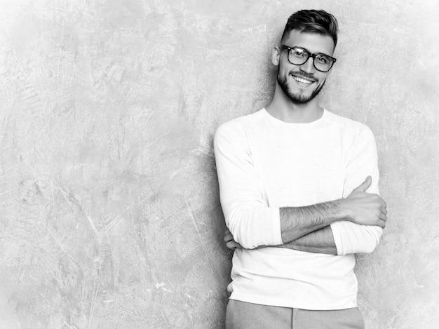 Portrait de beau modèle d'homme d'affaires souriant hipster portant des vêtements décontractés d'été blanc.
