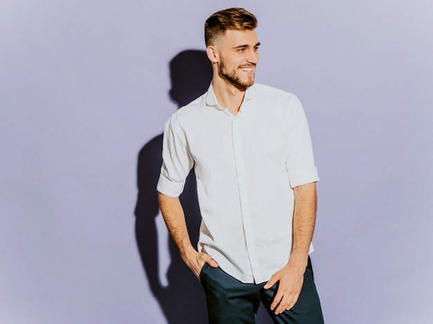 Portrait de beau modèle d'homme d'affaires souriant hipster vêtu d'une chemise d'été blanche décontractée.