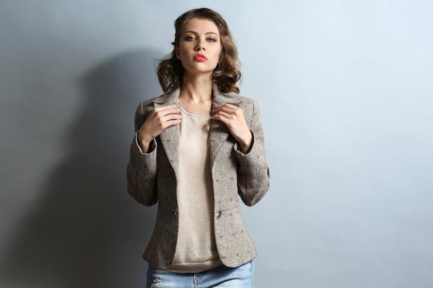Portrait de beau modèle en jeans et veste sur fond gris