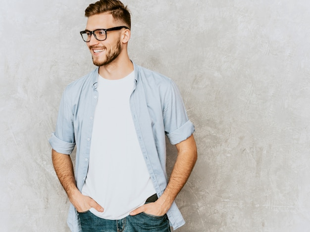 Portrait de beau modèle jeune homme souriant portant des vêtements de chemise décontractée. homme élégant de mode posant dans des lunettes
