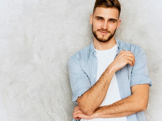 Portrait de beau modèle jeune homme souriant portant des vêtements de chemise décontractée. homme élégant de mode posant