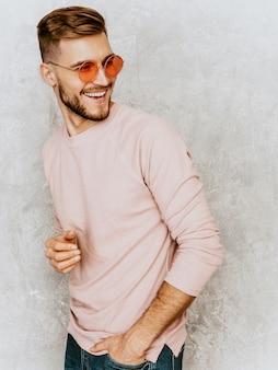 Portrait de beau modèle jeune homme souriant portant des vêtements décontractés d'été rose. homme élégant de mode posant dans des lunettes de soleil rondes