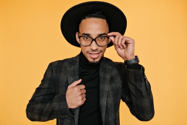 Portrait de beau modèle masculin aux yeux bruns touchant son chapeau de manière ludique. photo intérieure d'un homme africain bien habillé de bonne humeur.