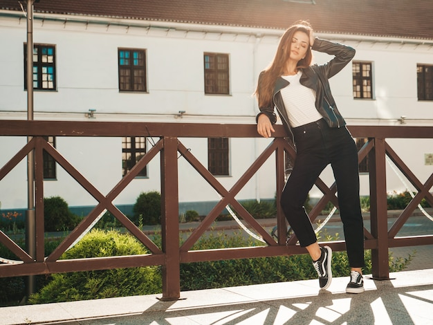 Portrait de beau modèle souriant. femme vêtue d'une veste en cuir noir hipster d'été et d'un jean. femme à la mode posant dans la rue