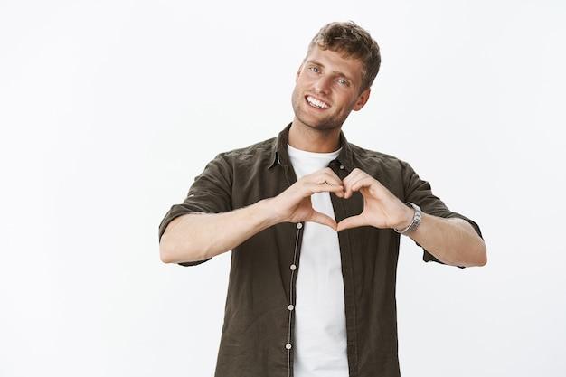 Portrait d'un beau petit ami masculin mignon et tendre souriant et inclinant la tête montrant le signe du cœur sur le corps, faisant une confession de sympathie et de sentiments romantiques sur un mur gris