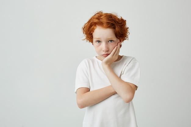 Portrait de beau petit enfant aux cheveux rouges et taches de rousseur tenant la tête avec la main