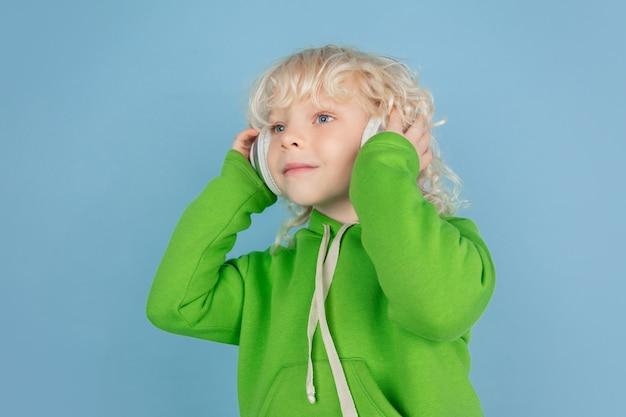 Portrait de beau petit garçon caucasien isolé sur mur bleu