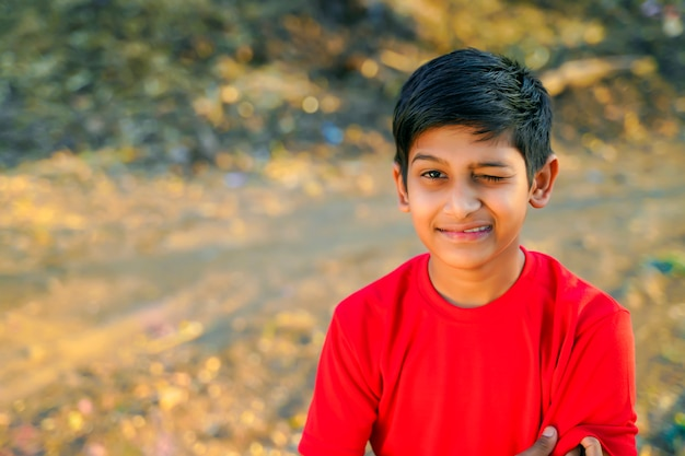 Portrait de beau petit garçon clignotant en t-shirt rouge
