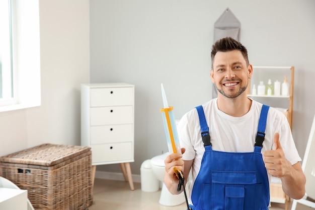 Portrait de beau plombier dans les toilettes