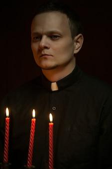Portrait de beau prêtre catholique ou pasteur avec collier de chien, fond rouge foncé.