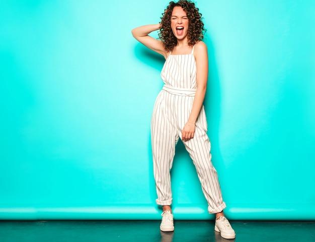 Portrait, de, beau, sourire, modèle, à, afro, boucles, coiffure, habillé, dans, été, hipster, vêtements., sexy, insouciant, girl, poser, près, mur bleu., tendance, drôle, et, positif, femme
