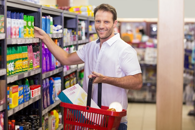 Portrait d'un beau sourire prenant un produit en rayon dans un supermarché