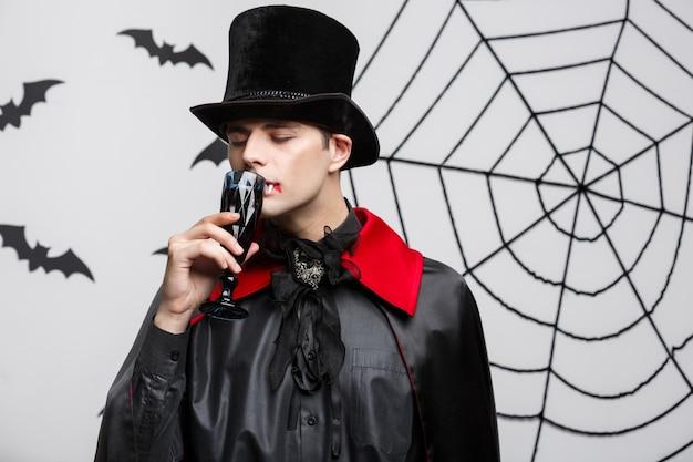 Portrait de beau vampire caucasien boire boire du vin rouge sanglant.