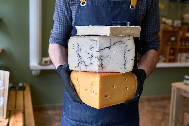 Portrait d'un beau vendeur de fromage en uniforme tenant trois gros fromages devant le magasin