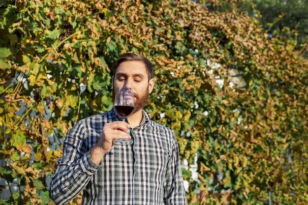 Portrait d'un beau vigneron tenant à la main un verre de vin rouge et le dégustant, vérifiant la qualité du vin tout en se tenant dans les vignes. petite entreprise, concept de fabrication de vin fait maison.