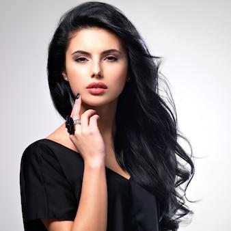 Portrait de beau visage d'une jeune femme aux longs cheveux bruns.