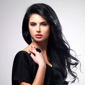 Portrait de beau visage d'une jeune femme aux longs cheveux bruns