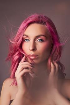 Portrait de beauté art d'une femme aux cheveux roses, coloration créative. des reflets aux couleurs vives et des ombres sur le visage, une fille avec des bijoux. cheveux teints au vent