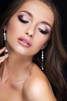 Portrait de beauté d'une belle brune sur fond noir