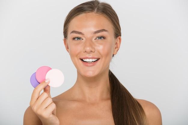 Portrait de beauté de belle femme torse nu avec de longs cheveux bruns souriant et tenant des tampons cosmétiques colorés, isolés
