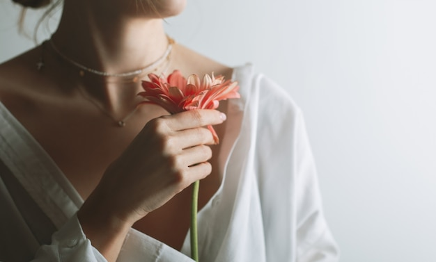 Portrait de beauté d'une belle jeune femme, posant avec fleur