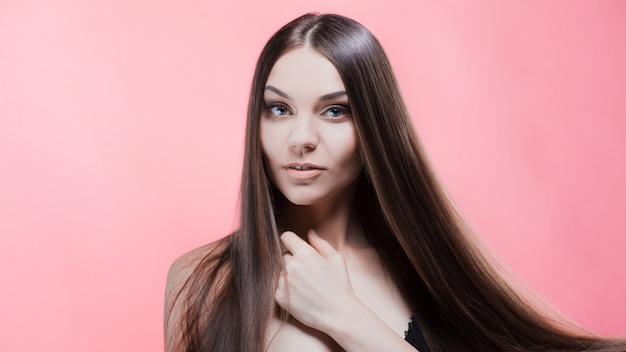 Portrait de beauté brune avec des cheveux parfaits, sur un mur rose. soin des cheveux