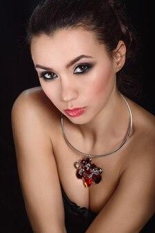 Portrait de beauté brune fille blanche sur fond noir avec des bijoux