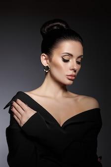 Portrait de beauté classique d'une femme avec un maquillage de soirée parfait sur fond sombre. peau parfaite sans rides, maquillage beauté professionnel, longs cils. fille parfaite en vêtements noirs