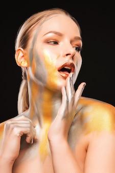 Portrait de beauté du modèle blond à la mode avec de la peinture or et argent
