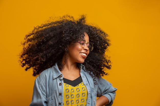 Portrait de beauté d'une femme afro-américaine avec coiffure afro et maquillage glamour. femme brésilienne. race mixte. cheveux bouclés. coiffure. mur jaune.